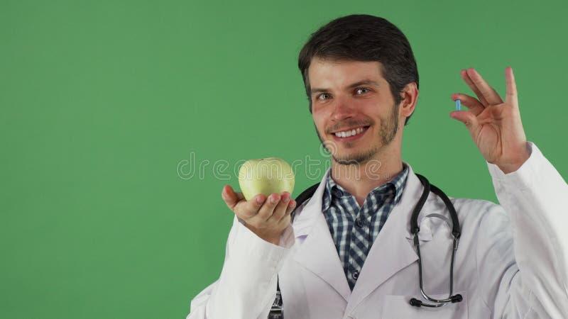 Doutor masculino alegre que guarda o comprimido da vitamina e uma maçã fotografia de stock