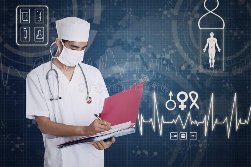 Doutor masculino asiático que faz anotações fotografia de stock royalty free