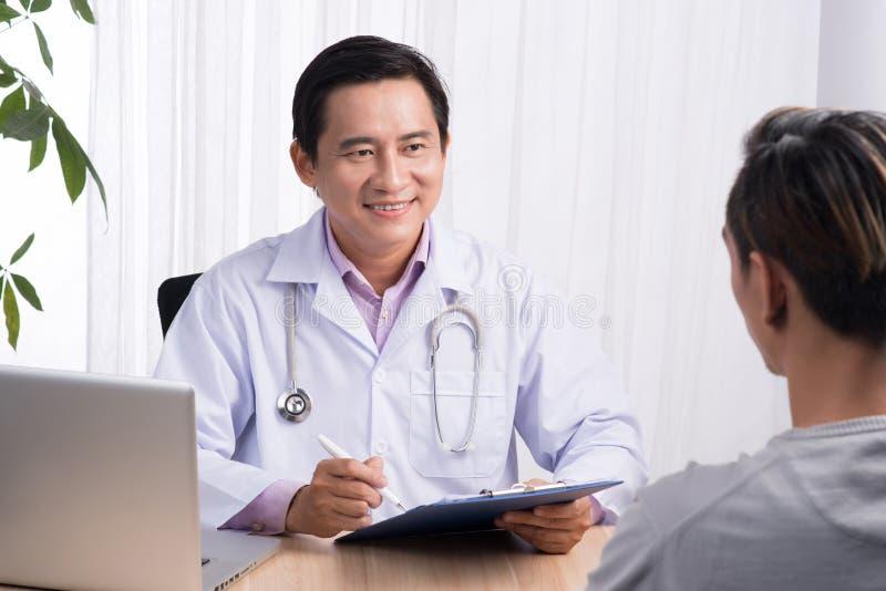 Doutor masculino asiático seguro que discute o diagnóstico com o paciente dentro foto de stock