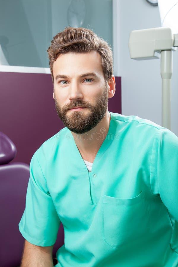 Doutor masculino com a barba no traje verde na clínica dental foto de stock royalty free