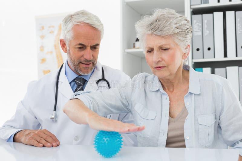 Doutor masculino com a bola de utilização paciente superior do imbecil do esforço foto de stock