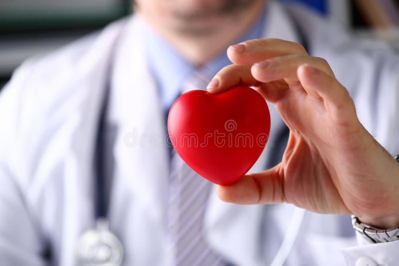 Doutor masculino da medicina para realizar no coração vermelho do brinquedo dos braços imagem de stock
