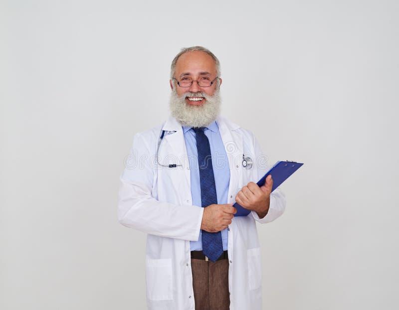 Doutor masculino de sorriso com um dobrador no uniforme que está contra o wh fotografia de stock