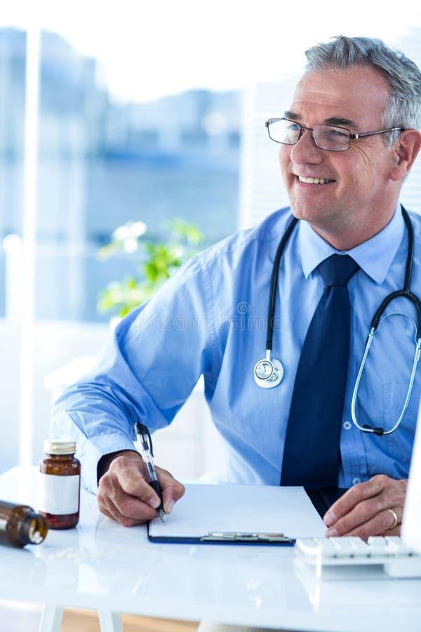 Doutor masculino de sorriso que olha afastado na clínica fotos de stock royalty free