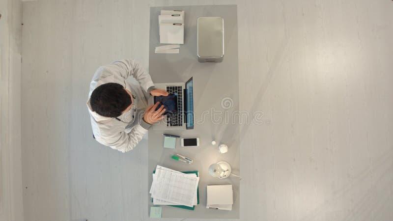 Doutor masculino de Timelapse que trabalha em uma tabela com um portátil Vista superior imagem de stock