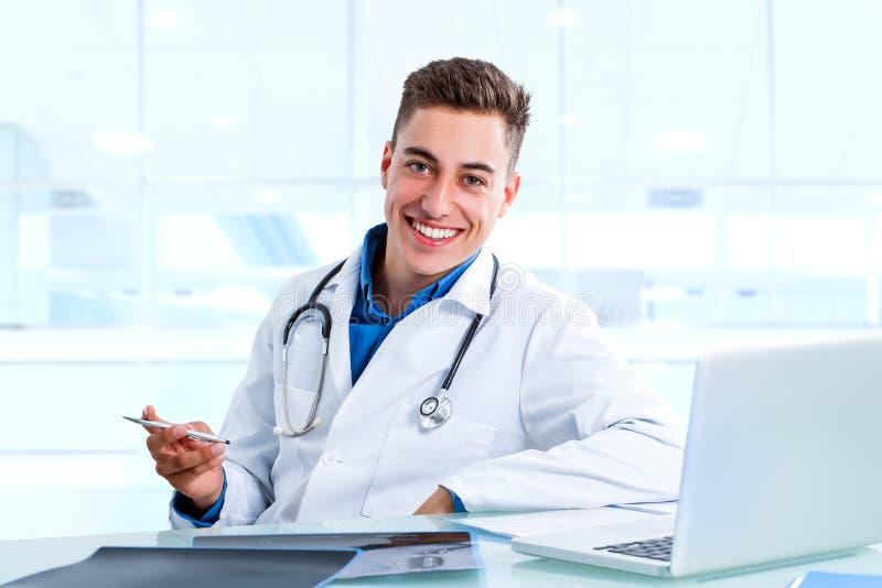 Doutor masculino médico na mesa com portátil e raios de x fotos de stock royalty free