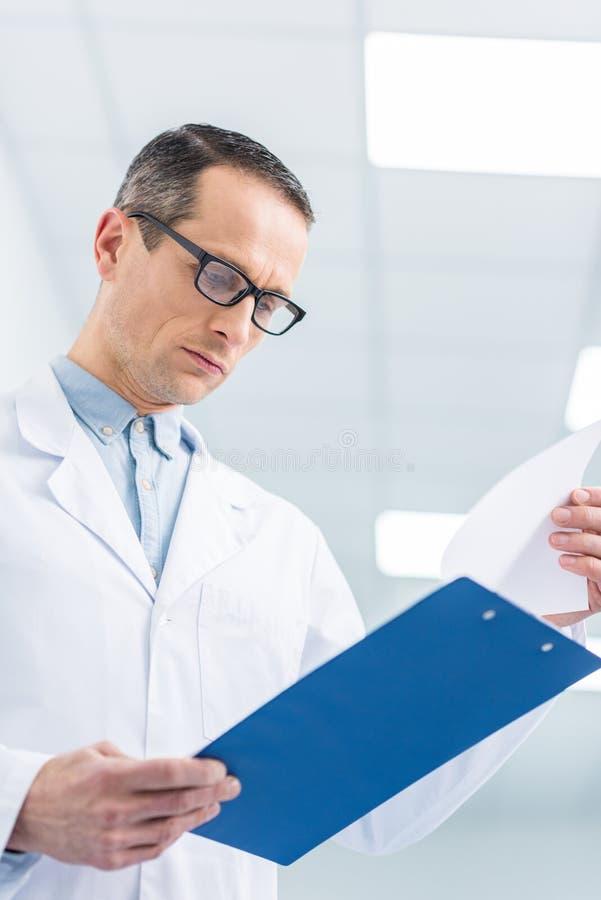 doutor masculino no diagnóstico branco da leitura do revestimento imagem de stock