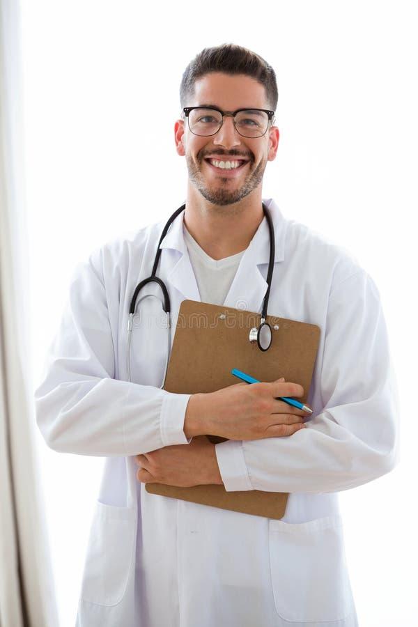 Doutor masculino novo atrativo com o estetoscópio sobre a prancheta da terra arrendada do pescoço isolada no branco fotografia de stock royalty free