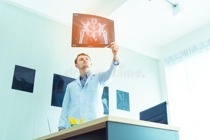 Doutor masculino novo que examina verificando o filme da radiografia do raio X de caixa do paciente no hospital da divisão Cirur fotografia de stock royalty free