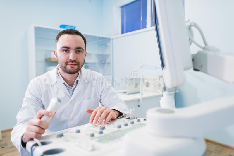 Doutor masculino novo que explica a varredura do ultrassom à mulher gravida no hospital fotografia de stock royalty free