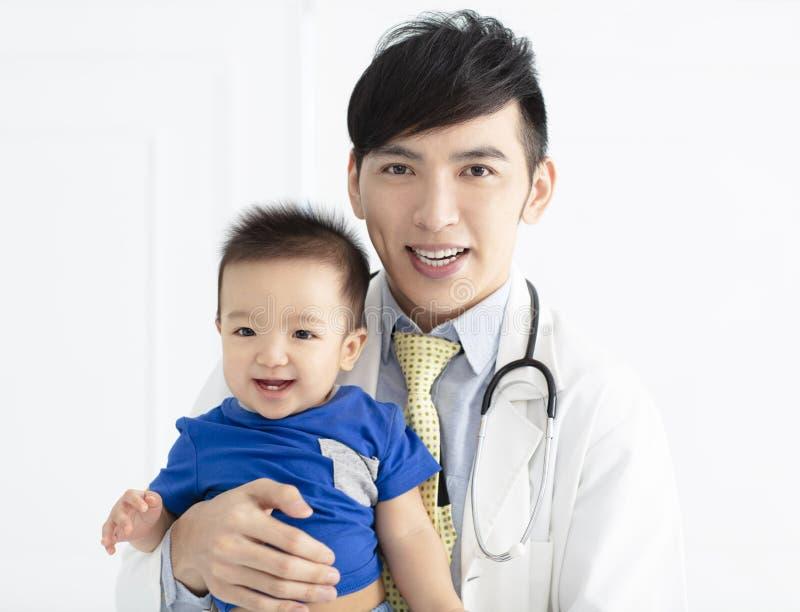 doutor masculino novo que guarda um bebê imagem de stock royalty free