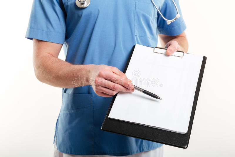 Doutor masculino ou enfermeira médica que apontam com a pena à prancheta da página vazia fotografia de stock