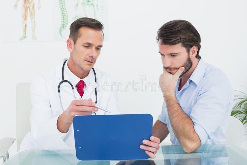 Doutor masculino que discute relatórios com o paciente na mesa fotografia de stock royalty free