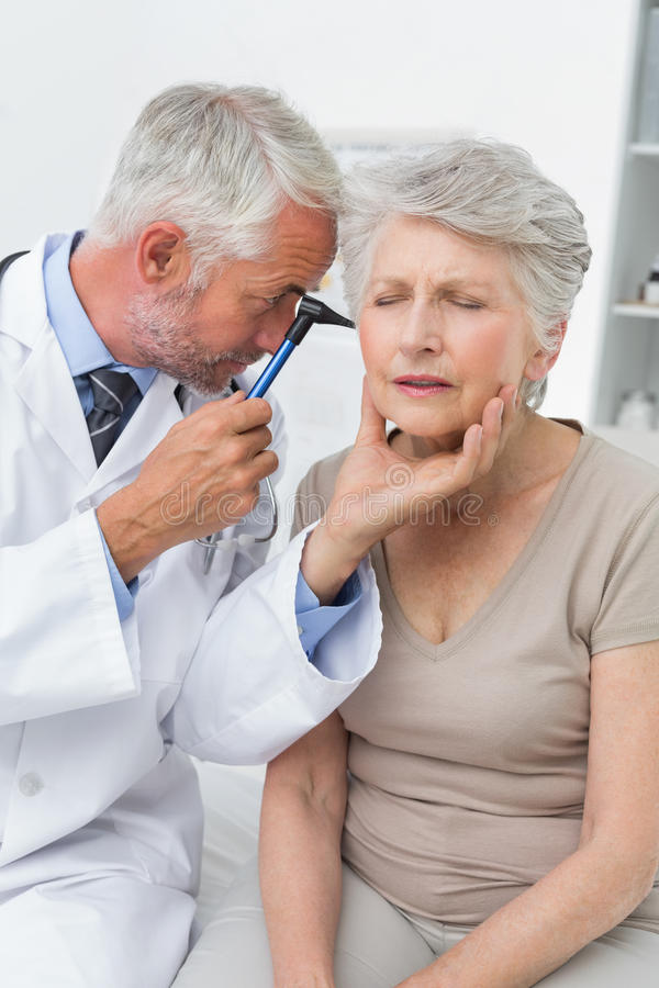 Doutor masculino que examina a orelha do paciente superior imagens de stock royalty free