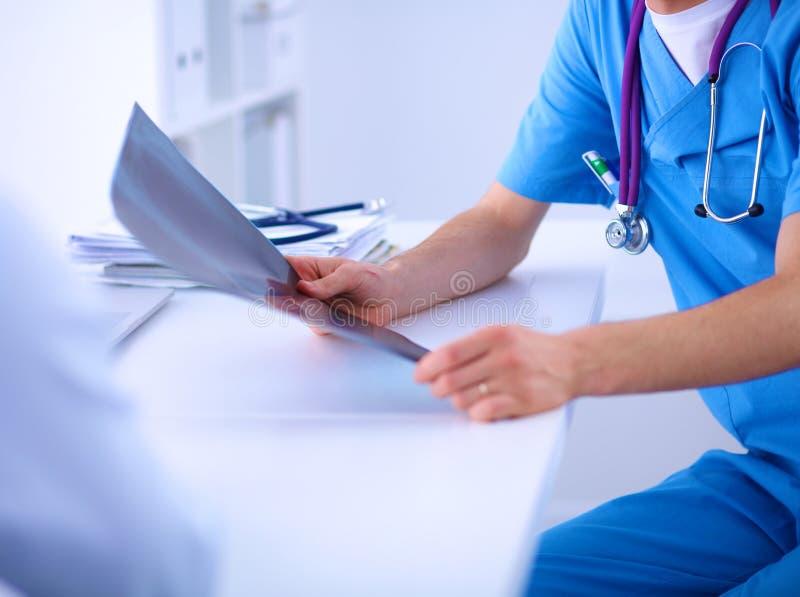 Doutor masculino que explica o raio X da espinha ao paciente dentro fotos de stock royalty free
