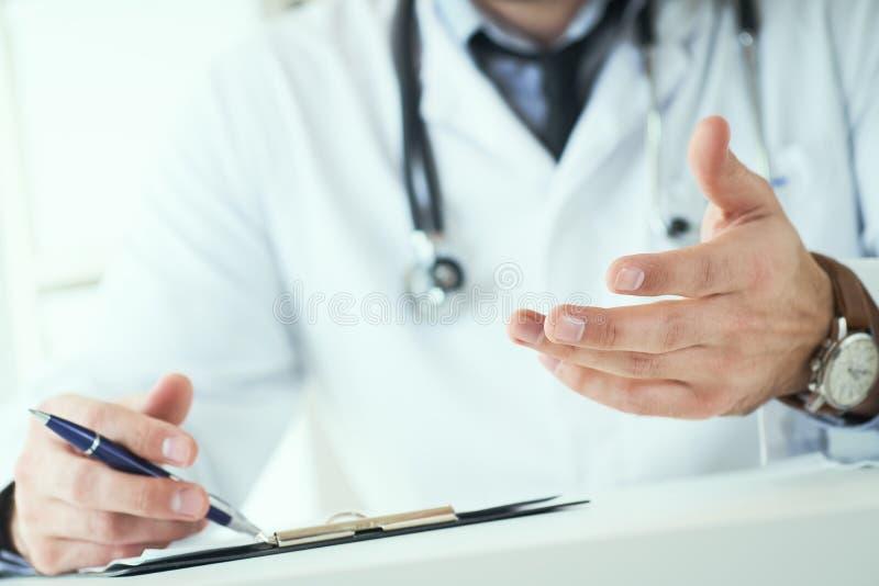 Doutor masculino que faz o gesto bem-vindo, paciente polidamente de convite para sentar-se para baixo no escritório médico Foto c foto de stock