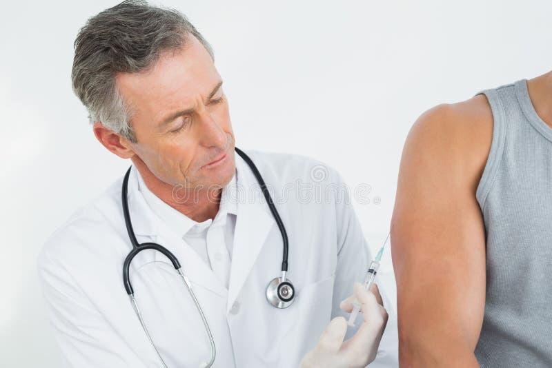 Doutor masculino que injeta um braço dos pacientes fotos de stock