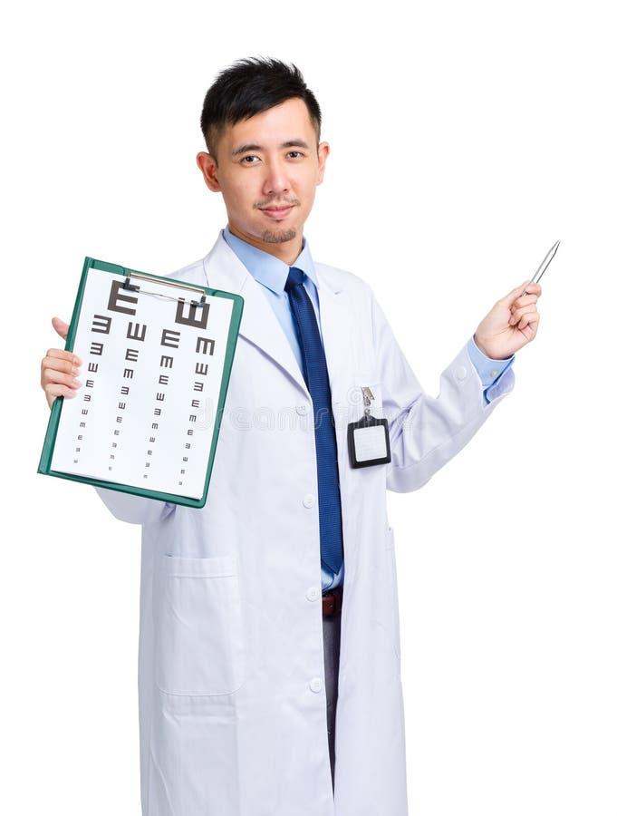 Doutor masculino que mantém a carta e a pena da optometria que apontam acima imagem de stock
