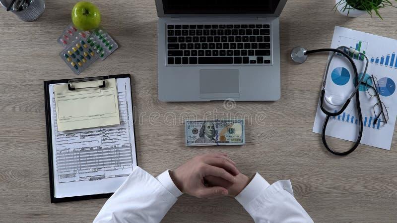 Doutor masculino que olha a opinião superior do dinheiro do dólar, custo da medicina, tentação do subôrno fotos de stock