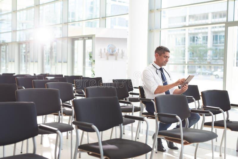 Doutor masculino que senta-se na cadeira e que usa a tabuleta digital em uma sala de conferências imagens de stock royalty free