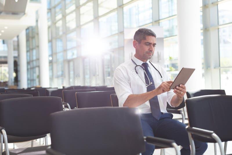 Doutor masculino que senta-se na cadeira e que usa a tabuleta digital na sala de conferências fotos de stock