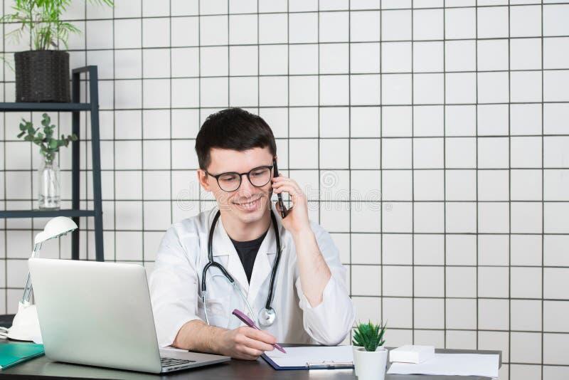 Doutor masculino que usa o telefone ao trabalhar no computador na tabela na clínica fotografia de stock