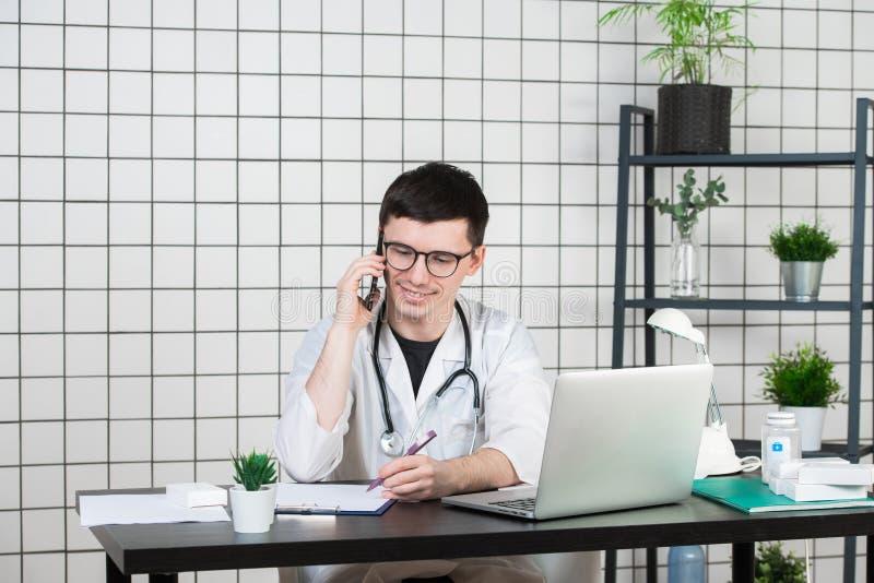 Doutor masculino que usa o telefone ao trabalhar no computador na tabela na clínica imagem de stock royalty free