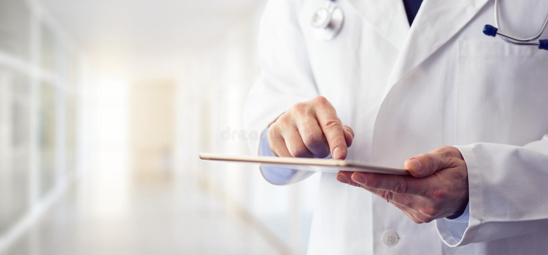 Doutor masculino que usa sua tabuleta digital imagens de stock
