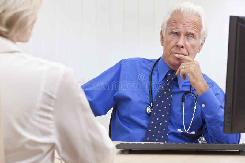 Doutor masculino sênior pensativo Com Computador imagem de stock