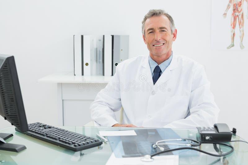 Doutor masculino seguro de sorriso na mesa no escritório imagens de stock royalty free