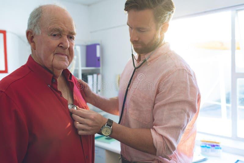 Doutor masculino seguro que verifica pulsação do coração pacientes superiores na clínica foto de stock