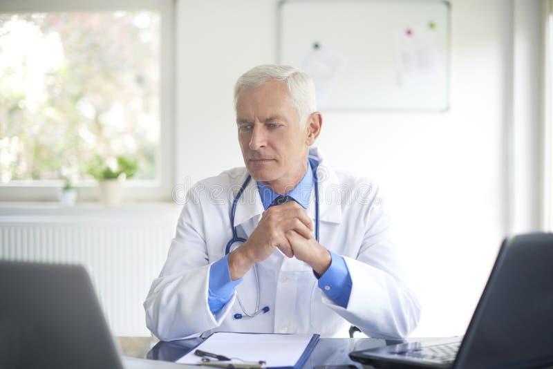 Doutor masculino superior que trabalha na sala de consulta imagens de stock royalty free