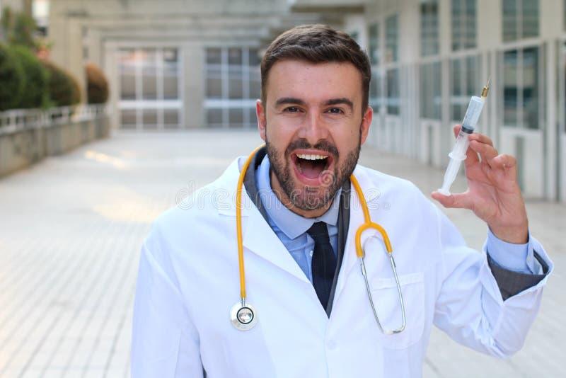 Doutor mau que guarda uma seringa no hospital imagens de stock