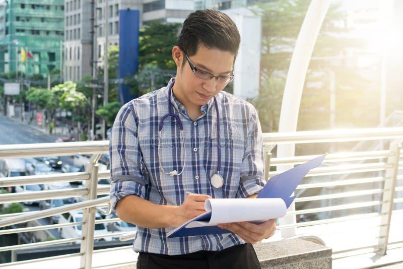 Doutor na camisa com estetoscópio que escreve a carta paciente foto de stock