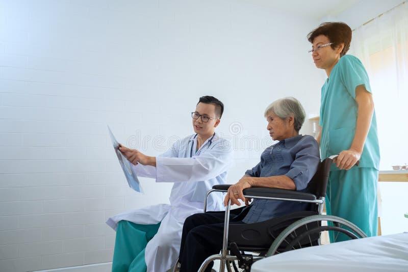 Doutor no escritório que examina um raio X e que discute com um SE fotos de stock royalty free