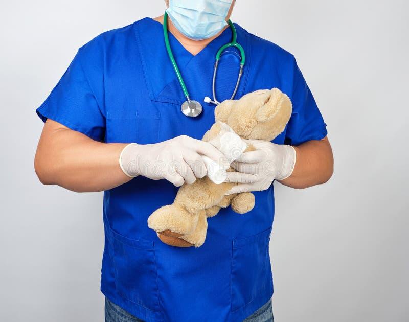 doutor no urso de peluche médico branco do marrom da pata da atadura das ataduras uniformes azuis fotografia de stock