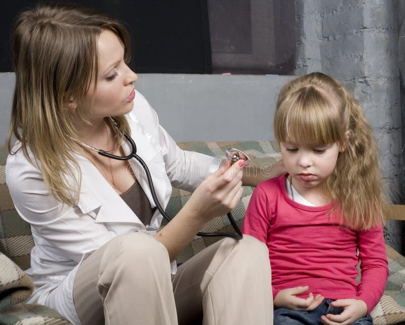 Doutor novo com inspeção médica má do sentimento paciente da menina com estetoscópio imagens de stock royalty free
