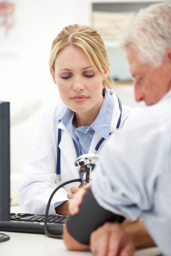 Doutor novo com paciente sênior imagem de stock royalty free