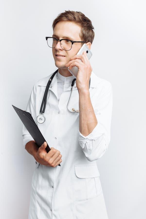 Doutor novo e considerável que fala no telefone com pacientes, estudante do interno com dobrador à disposição, fundo branco, para imagem de stock
