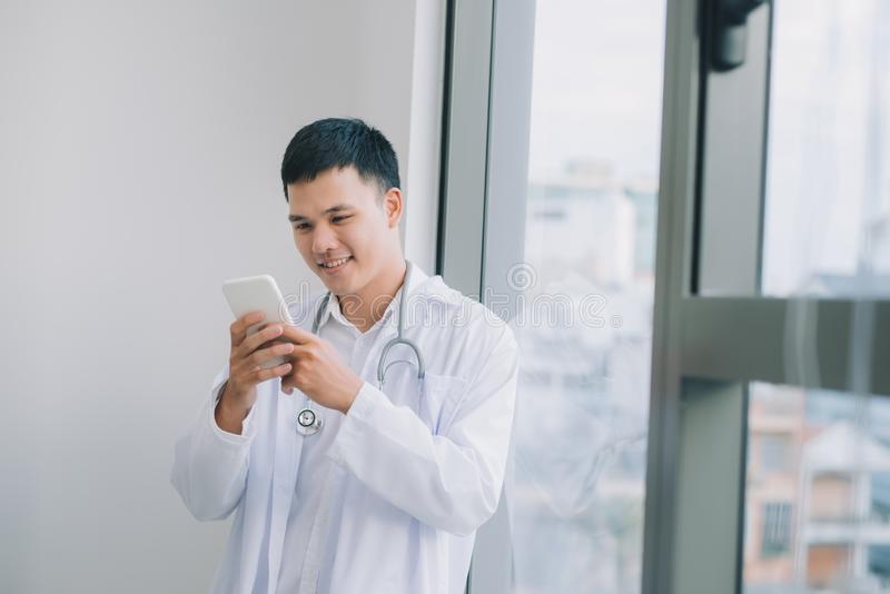 Doutor novo feliz que guarda o telefone celular imagem de stock royalty free