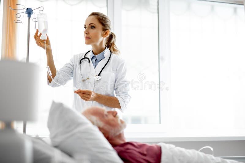 Doutor novo que ajusta a garrafa da infusão quando descanso paciente fotografia de stock royalty free