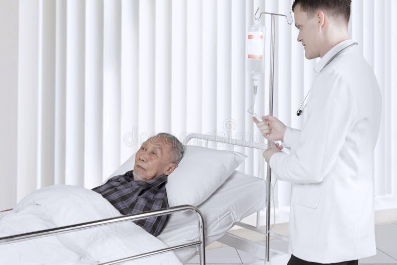 Doutor novo que ajusta a infusão na sala de recuperação fotos de stock royalty free