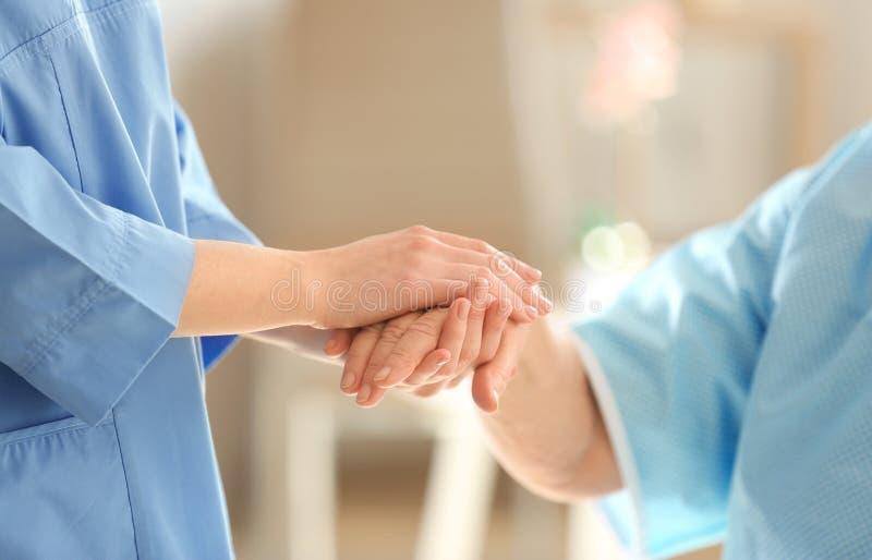 Doutor novo que guarda a mão da mulher idosa fotos de stock