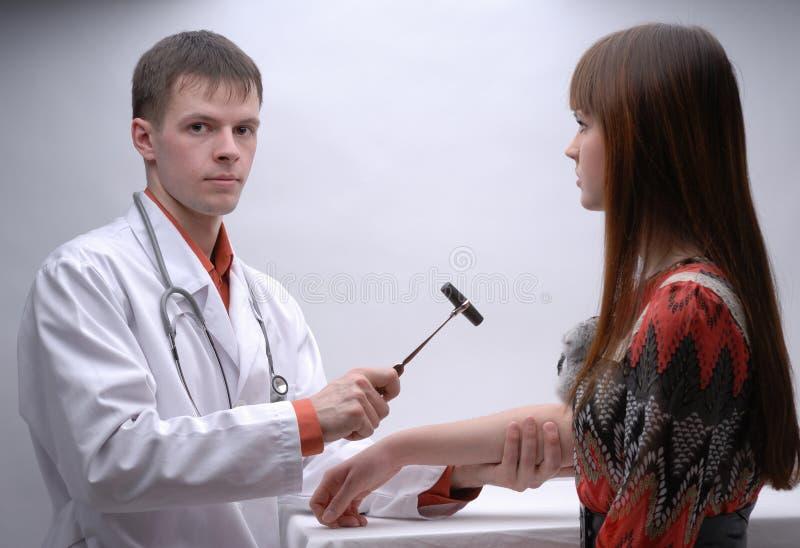Doutor novo que inspeciona o sistema nervoso do paciente foto de stock