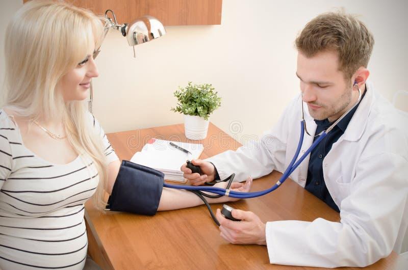 Doutor novo que verifica a pressão sanguínea do paciente fêmea imagem de stock royalty free