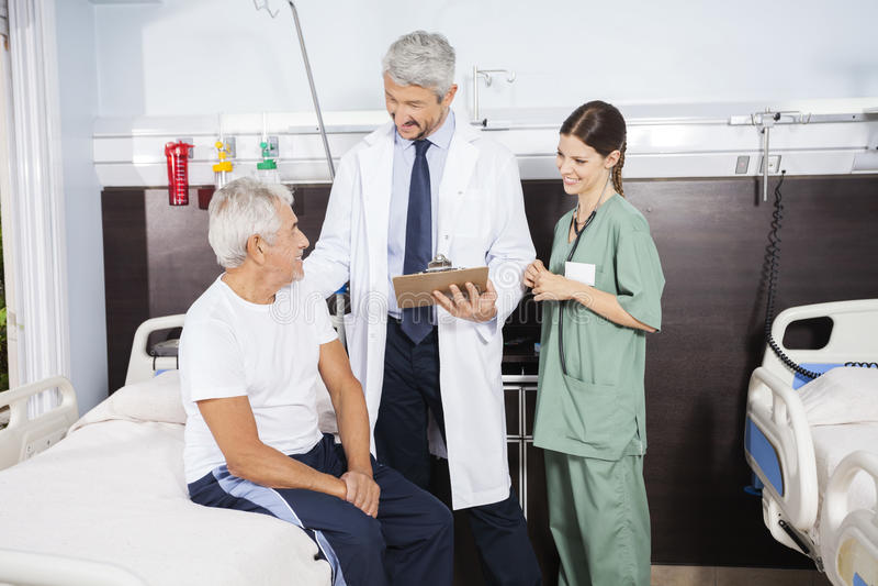 Doutor And Nurse Looking no paciente no centro de reabilitação imagens de stock royalty free