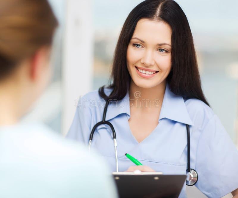 Doutor ou enfermeira de sorriso com paciente imagem de stock royalty free