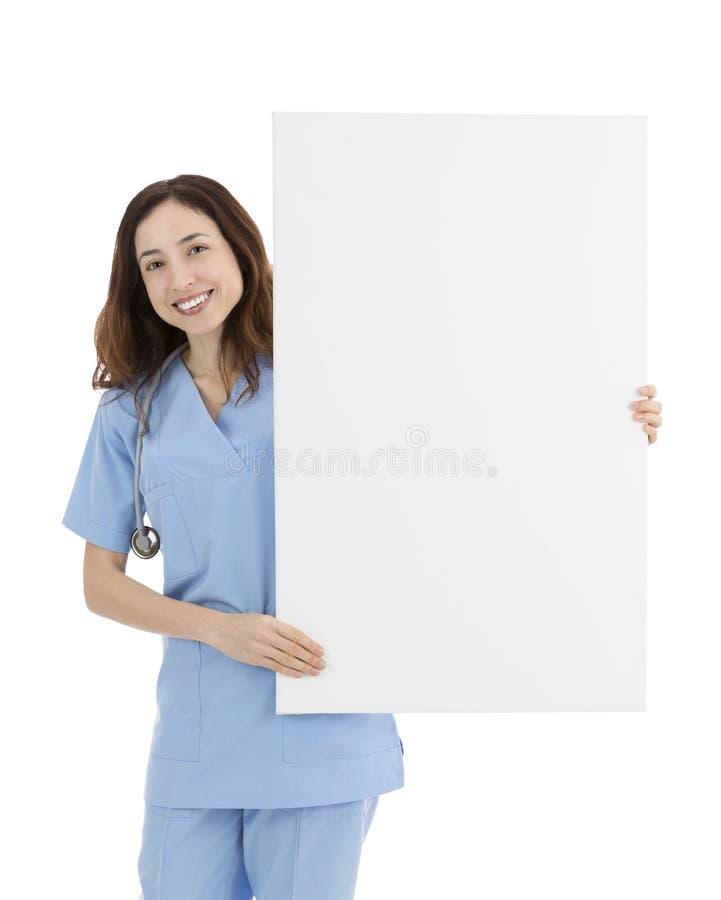 Doutor ou enfermeira fêmea amigável de sorriso que mostram um bi branco vazio fotos de stock