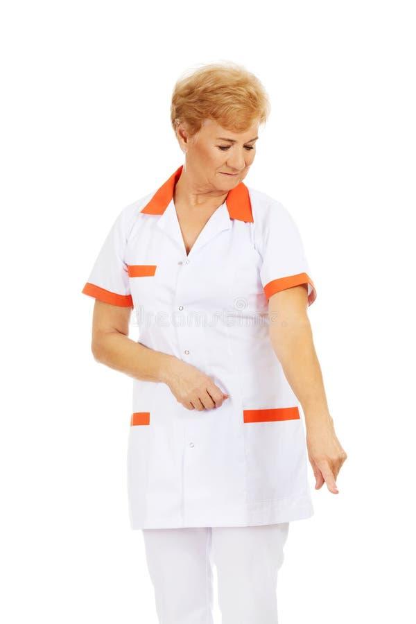 Doutor ou enfermeira fêmea idosa do sorriso que apontam para baixo imagens de stock