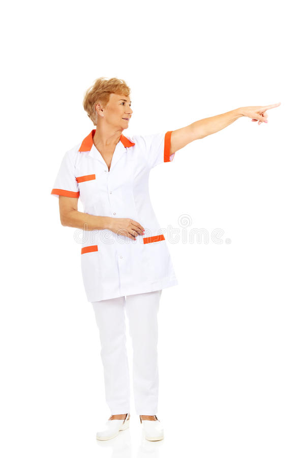 Doutor ou enfermeira fêmea idosa do sorriso que apontam para o copyspace ou o algo foto de stock royalty free